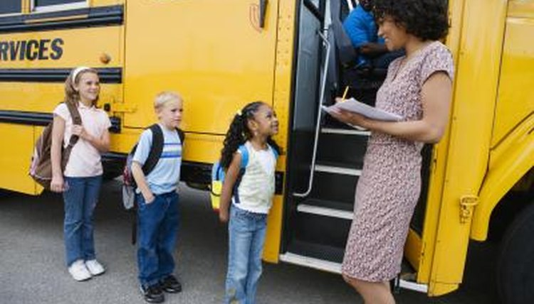 Teacher taking attendance as young students get on bus for field trip
