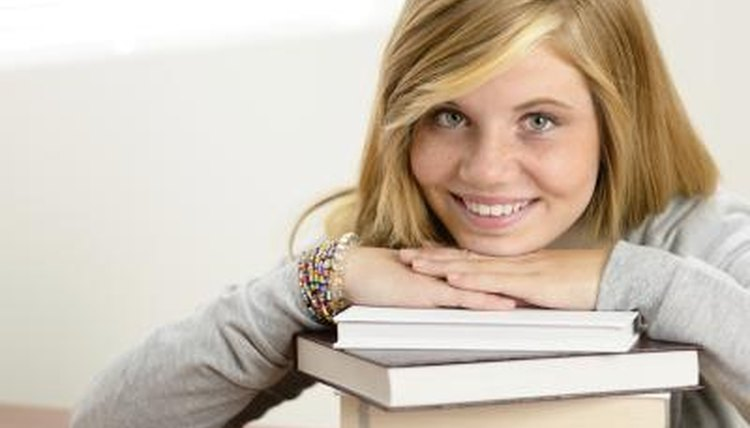 High school smiling while leaning on top of stack of books