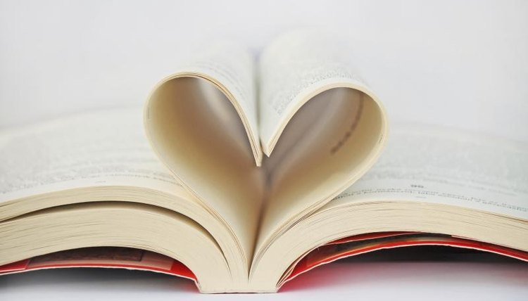 An open book with pages forming the shape of a heart.