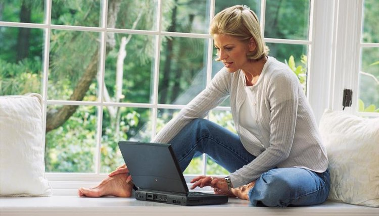 Woman working on laptop in front of window.