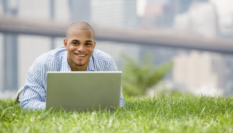 Doctorate student typing on laptop while laying in the grass.