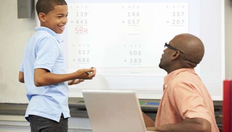 A student working at an interactive whiteboard while the teacher is tutoring him.