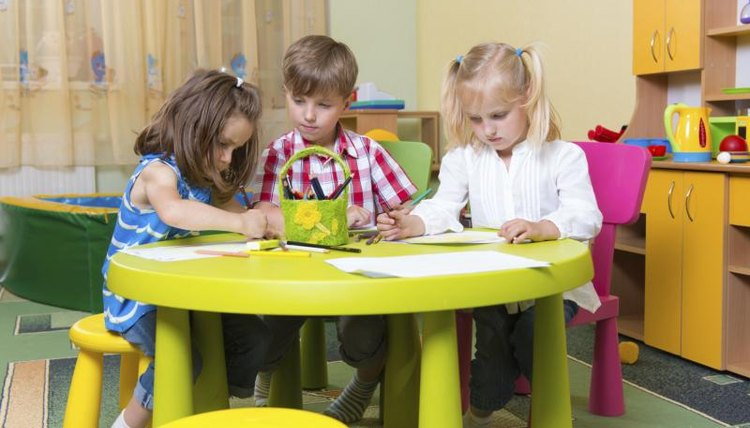 Preschool students sitting at table in classroom.