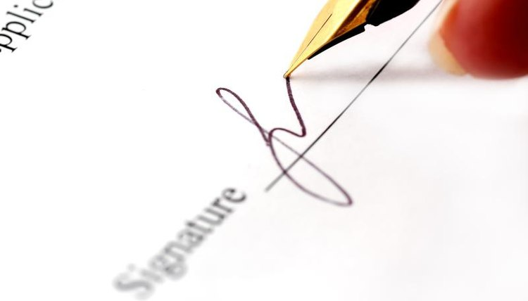 Close-up of a signature being written on a document.