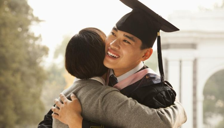 Smiling young graduate hugging his mother.