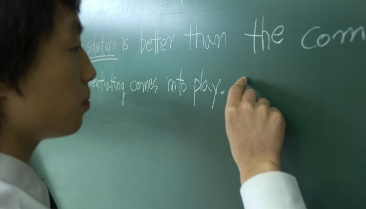Student writing on chalkboard in English class.