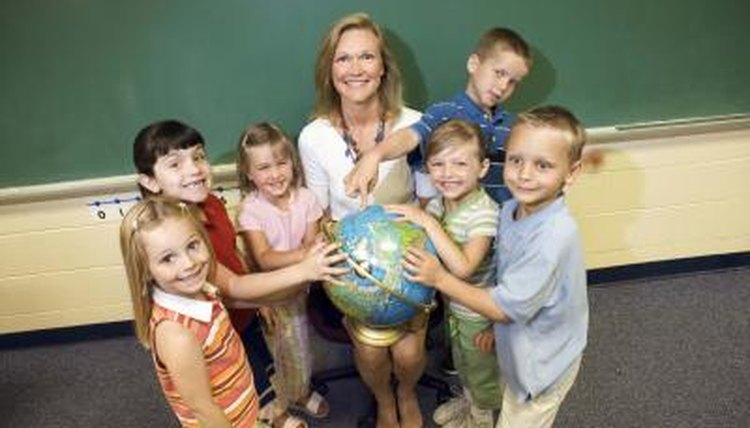 Teacher and students holding a globe in the classroom.