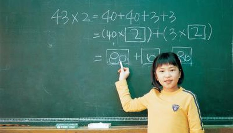 Singapore student practicing math problem on chalkboard