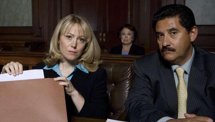 A female lawyer and male client sitting next to each other in a courtroom