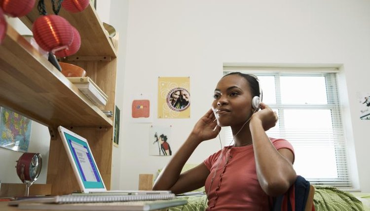 Young woman in dormitory sitting in front of a computer with headphones.
