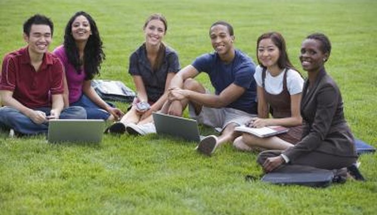 Smiling students studying together on campus lawn.