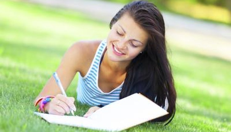 Student writing in notebook while laying on grass lawn