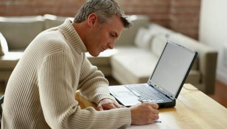 Man working on laptop from home while taking notes