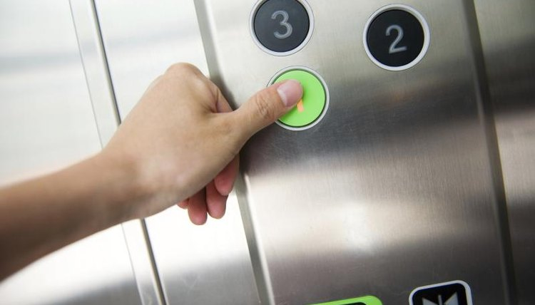 Woman pushing a button in an elevator.