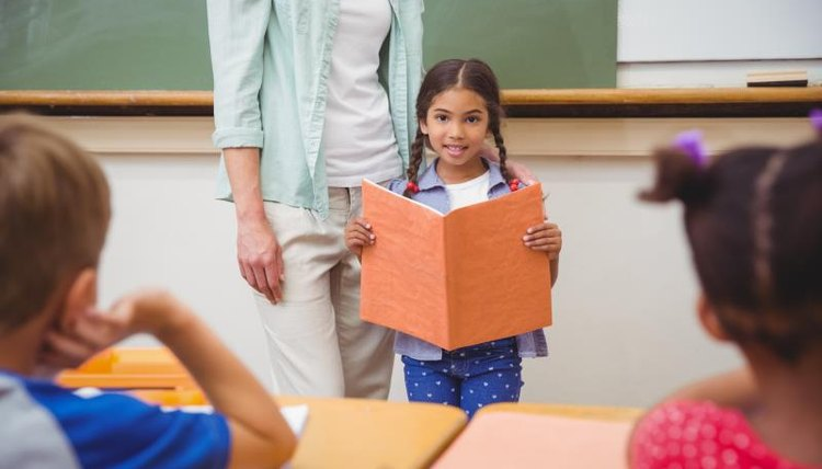 Elementary school student standing in class giving presentation