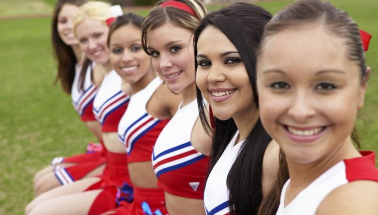 Smiling cheerleaders sitting on bench.