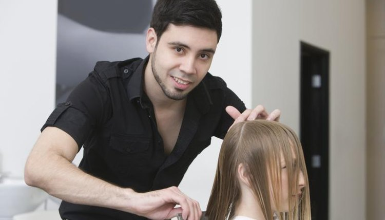Male hairstylist cutting hair in the salon.