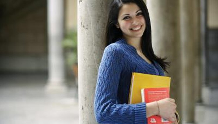 College student holding books on campus