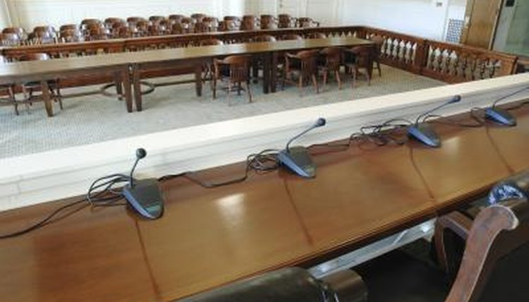 A row of microphones set up in the front of a courtroom.