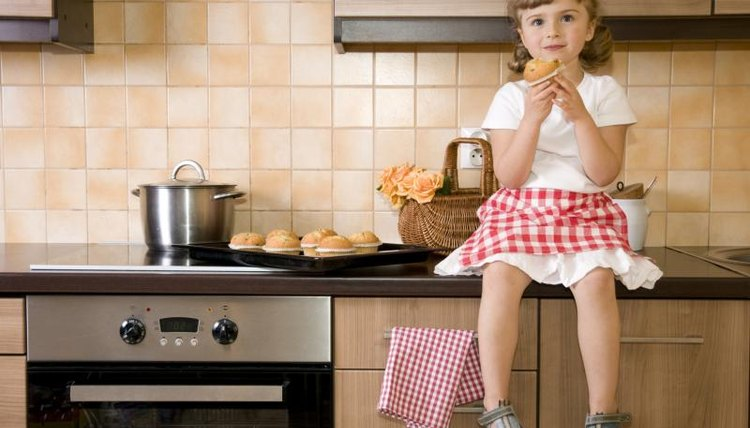 Young girl eating a muffin while sitting on a kitchen counter.