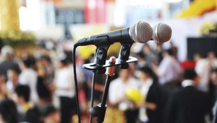 Close-up of microphone in large auditorium.