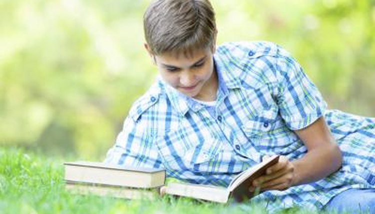 Teenager reading book on grass