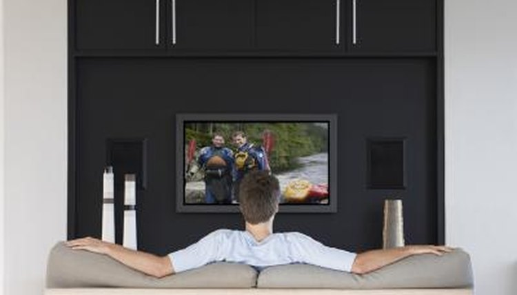 Rear view of a man watching TV on his modern home theater system