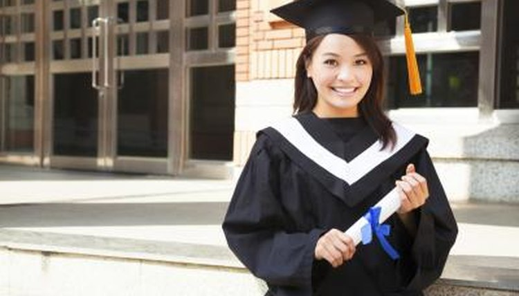 Graduating student standing in gown with degree