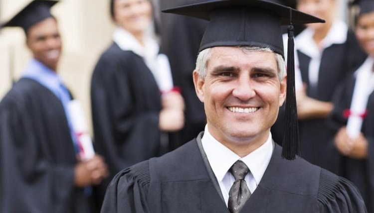 A Dean standing in front of graduates during a commencements ceremony.