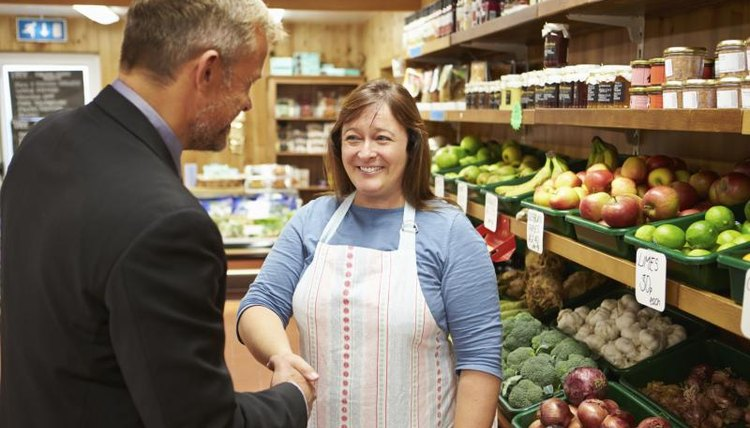 An insurance agent shaking hands with a store owner.