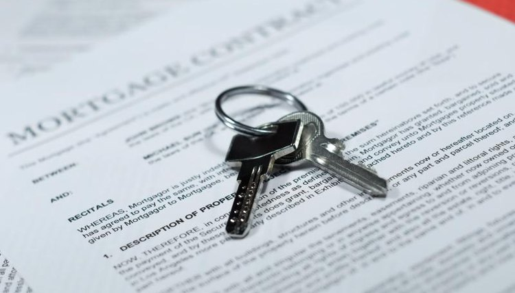 A close-up of house keys on paperwork.