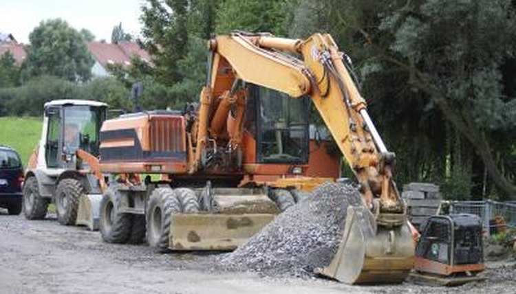 Construction worker using heavy equipment to move rocks
