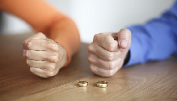 Divorced couple taking off wedding rings.