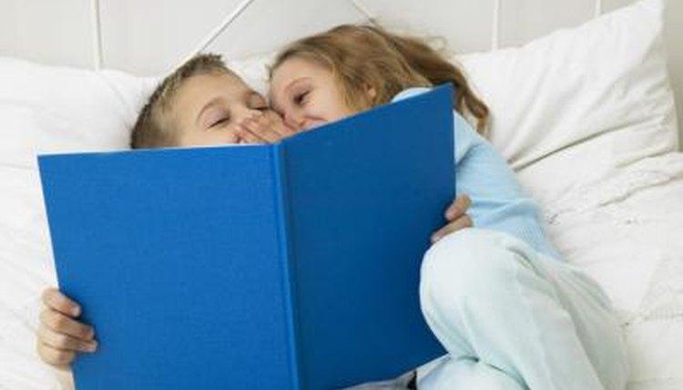 Children reading a book together in bed.