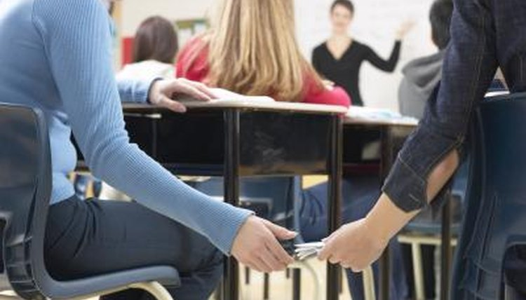 Students passing notes in a classroom.