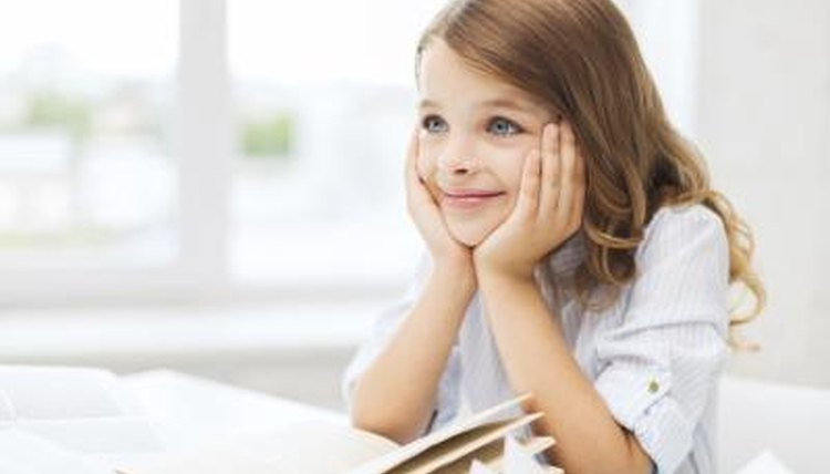 Child smiling in front of book