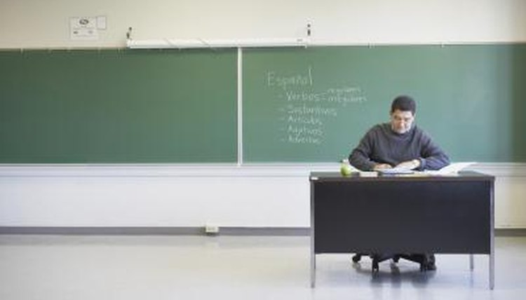 A teacher works at his desk in an empty classroom.