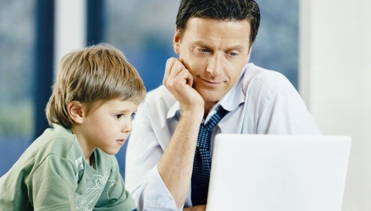 Son looking at laptop in office with father.