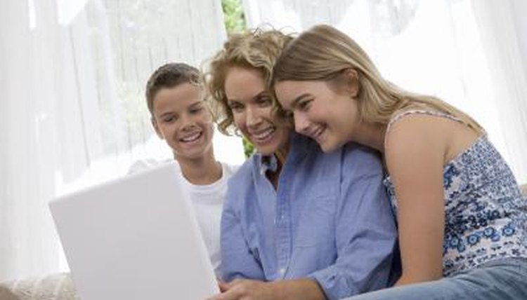 Mother using laptop beside her two children.