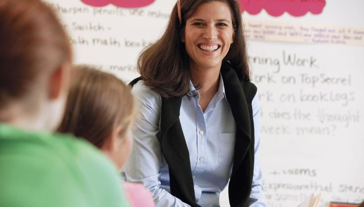 Smilling teacher in classroom of young students