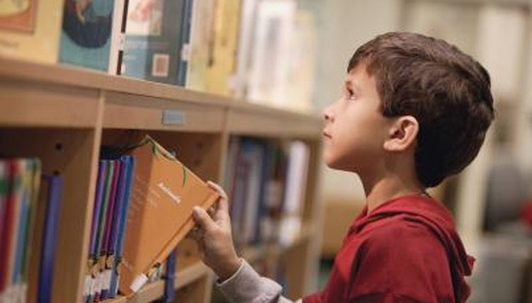 A young boy selecting a book to read at the library.