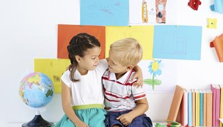 Young boy and girl student hugging in classroom