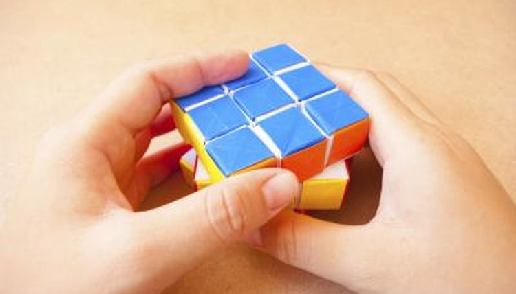 Hands playing with Rubik Cube on table