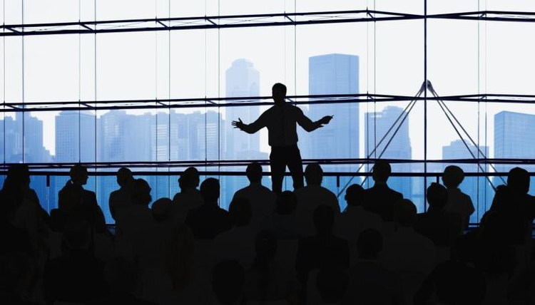An individual is giving a presentation in front of a crowd.