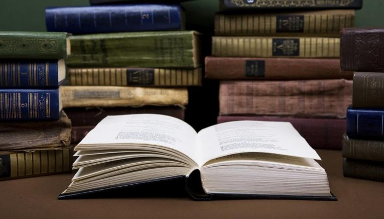 A classic novel is open in front of other classically bound books.