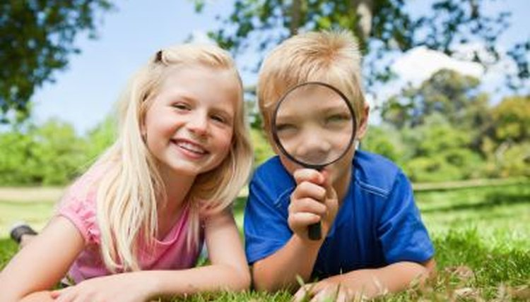 Two children holding up magnifying glass