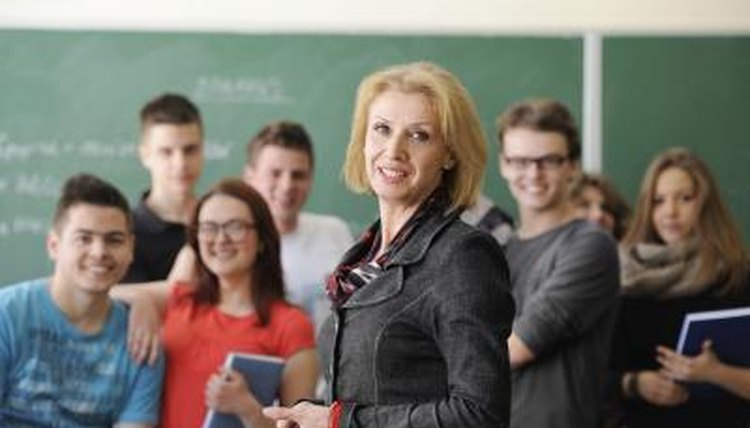 Smiling teacher standing in front of class.