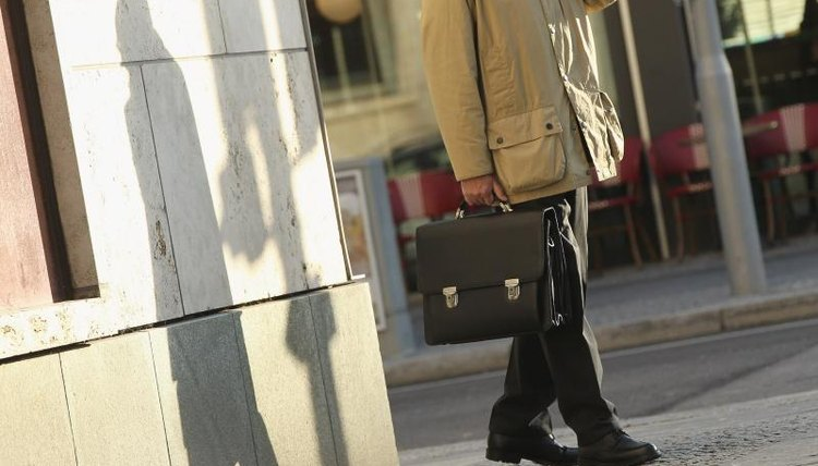 A  man carrying a briefcase walking around a corner.