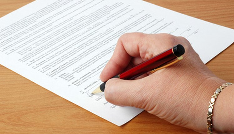 Woman's hand holding red pen to sign document