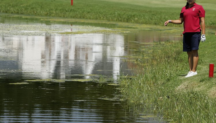 Jennie Lee searches for her ball in a lateral water hazard defined by red stakes at South Africa's De Zatze Golf Club.